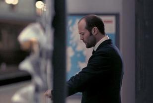 Jason Statham looking at his wristwatch in The Bank Job