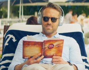 Ryan Reynolds is reading the book The Secret by Rhonda Byrne, and wears yet unidentified sunglasses.
